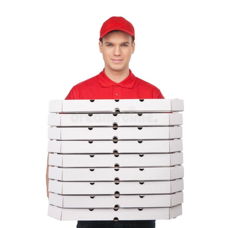La vostra pizza! Giovane uomo allegro della pizza che tiene una pila di pizza BO fotografie stock