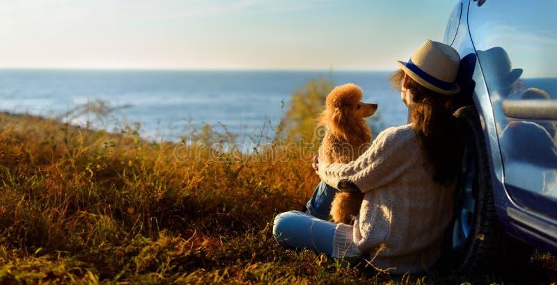 La voyageuse de femme avec le chien apprécie le beau coucher du soleil sur la mer pendant le voyage par la route photos libres de droits