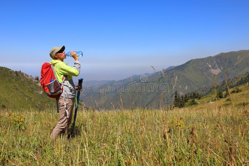 La voyageuse de femme boit l'eau d'une bouteille photographie stock libre de droits