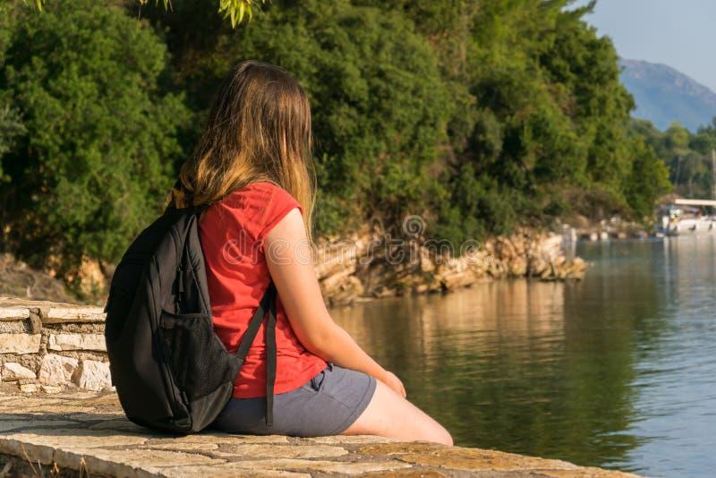 La voyageuse de fille, apprécie la vue de la mer, roches, conifères images libres de droits