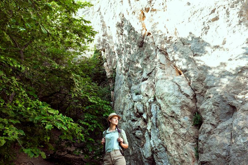 La voyageuse de fille marche par les montagnes et les bois Il sourit Les shorts verts de chemise et se bronzent Chapeau de paille images stock
