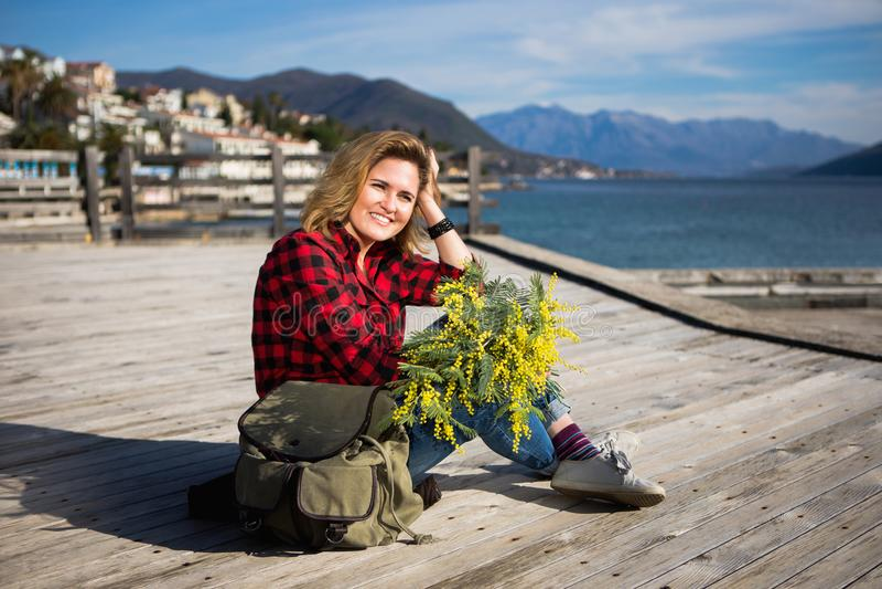 La voyageuse heureuse de fille s'assied sur un pilier en bois et tient un bouquet des fleurs de la mimosa dans des mains photo stock