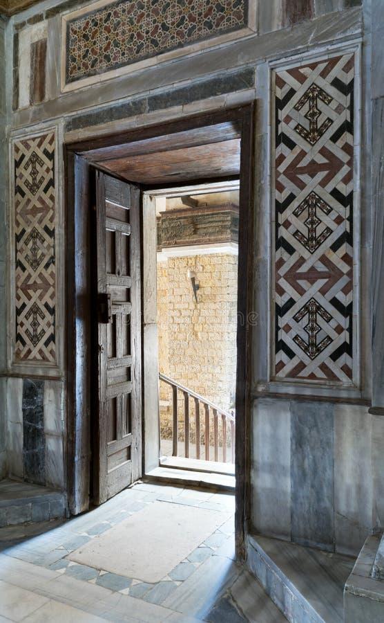 La vue à angles d'une porte ouverte fleurie âgée en bois menant à un passage avec la lumière lumineuse, couleur a décoré le mur d photo libre de droits