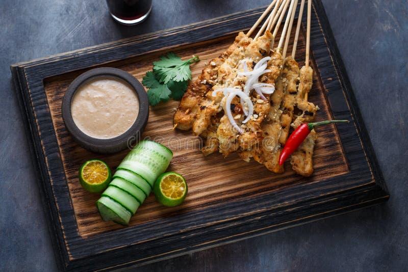 La vue étroite des brochettes malaisiennes de poulet - satay ou assouvissent l'ayam avec de la sauce à arachide, fond foncé images stock