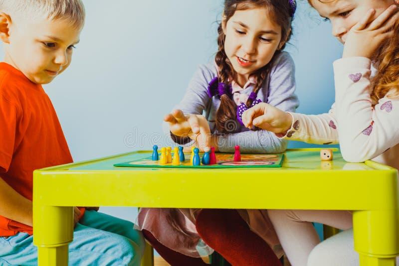 La vue étroite des enfants fait face autour de la table avec le jeu de société images libres de droits