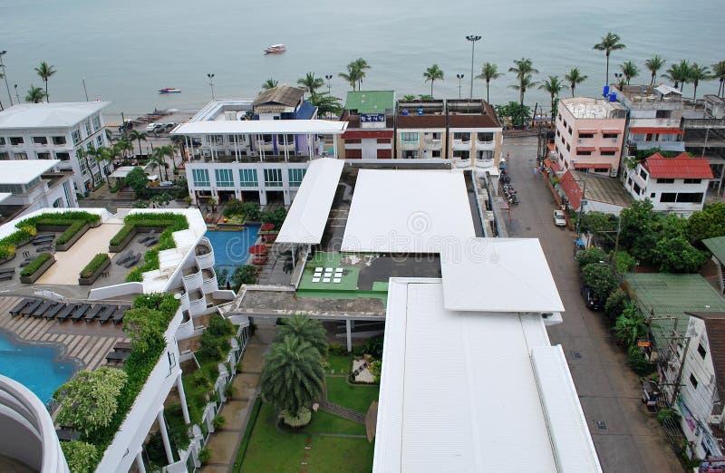 La vue aérienne d'un territoire de piscine d'hôtel, les bâtiments de voisinage et le Jomtien échouent à Pattaya, Thaïlande image libre de droits
