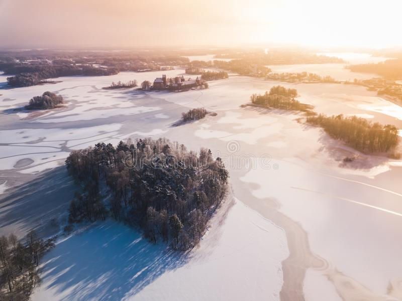 La vue aérienne de la neige d'hiver a couvert la forêt et le lac congelé d'en haut capturés de bourdon en Lithuanie photographie stock