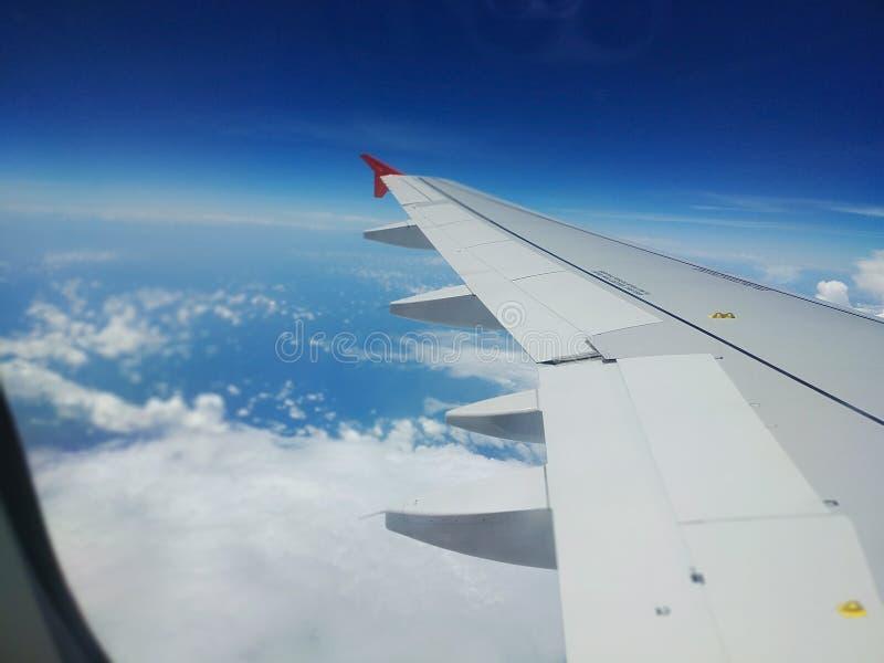La vue aérienne du ciel bleu de nuage et l'avion s'envolent la vue par la fenêtre d'avion image stock