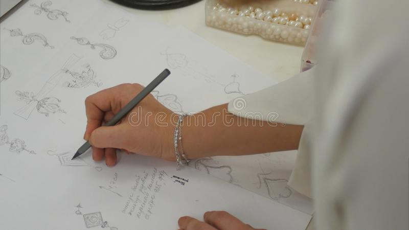 La vue aérienne regardant en bas du concepteur de bijoux dans le studio esquissant conçoit photo stock