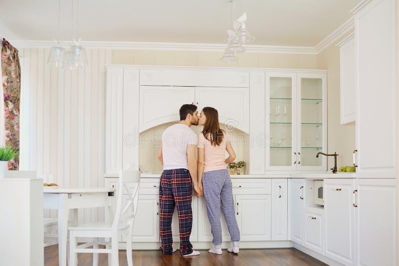 La vue arrière d'un jeune couple dans des pyjamas se tiennent dans la cuisine photographie stock libre de droits