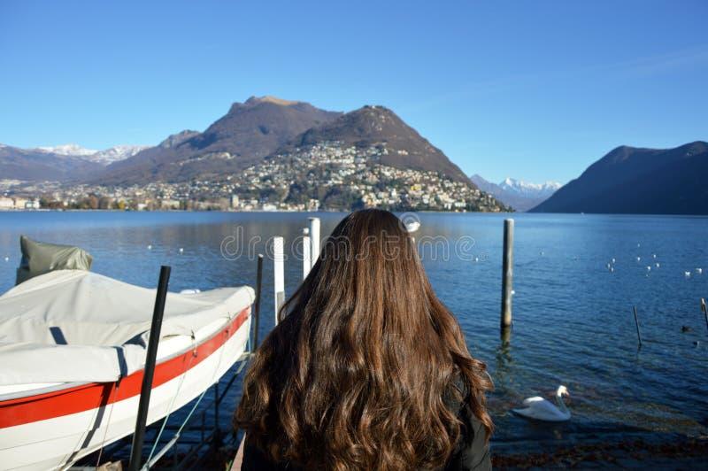 La vue arrière de la femme marchant sur le pilier avec l'hiver vêtx, lac Lugano, Suisse, l'Europe photo stock