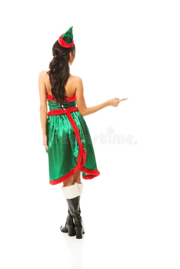 La vue arrière de l'elfe de port de femme vêtx l'indication la droite photographie stock libre de droits