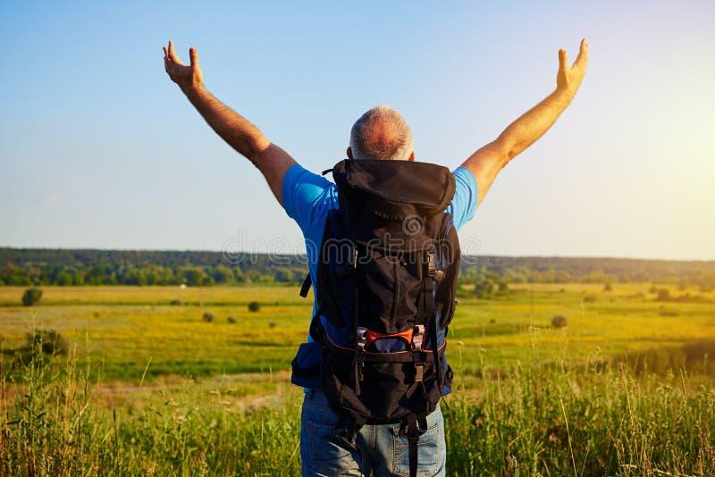 La vue arrière de l'homme âgé avec le sac à dos dans le domaine avec des mains se soulèvent photo stock
