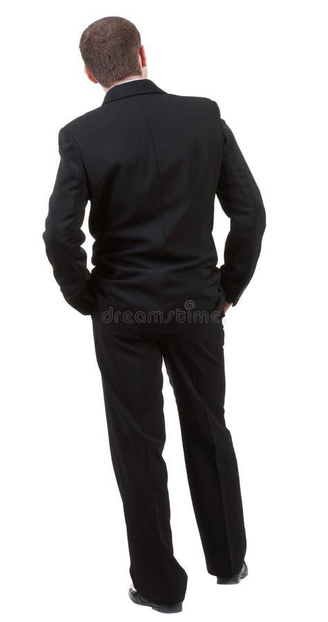 La vue arrière de l'homme d'affaires pense à l'avenir. Jeune type dans le costume noir image libre de droits
