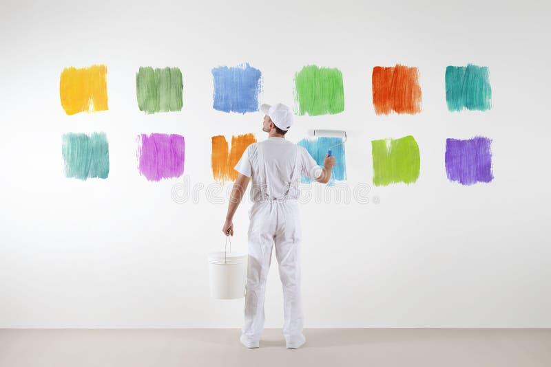 La vue arrière de l'homme de peintre qui font et choisit de diverses couleurs images stock