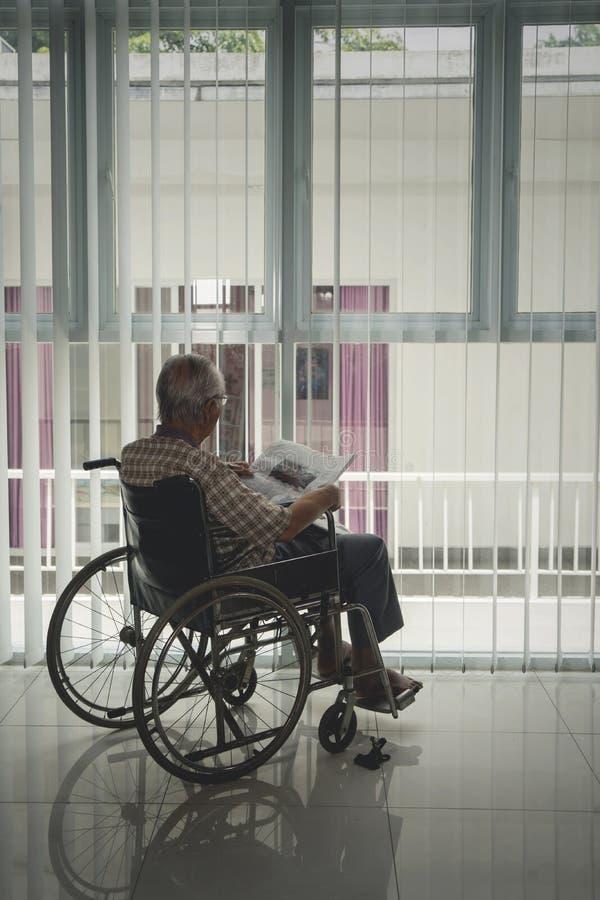 La vue arrière de l'homme supérieur handicapé lit un journal photos stock