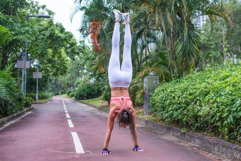 La vue arrière de la femme de forme physique faisant l'exercice d'appui renversé tenant tout droit les bras tendus garent la ruel image stock