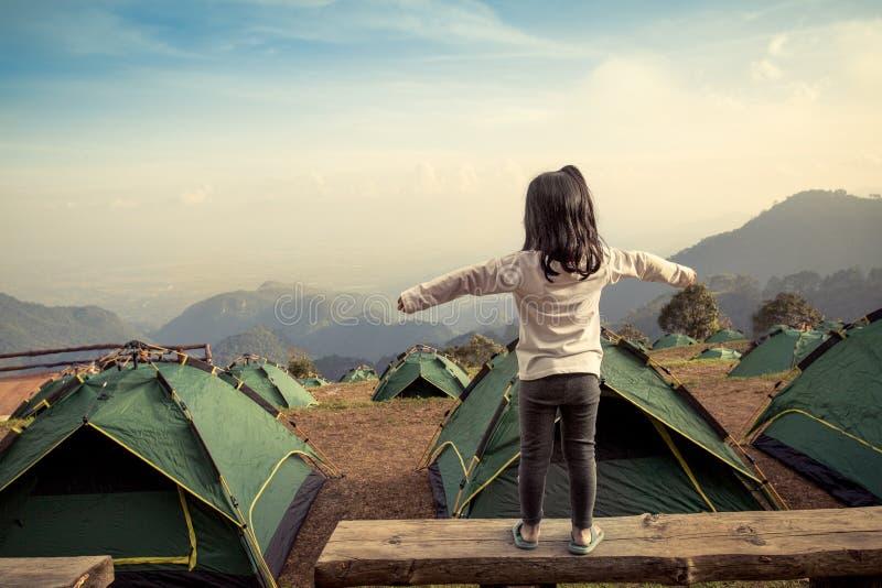 La vue arrière de la fille asiatique augmentent ses bras dans le camping photos stock