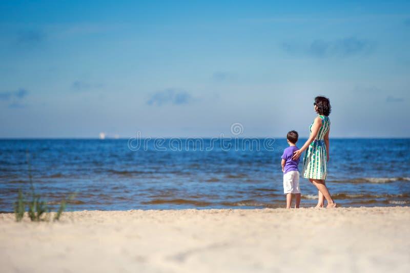 La vue arrière de la mère et son fils à l'été échouent images libres de droits