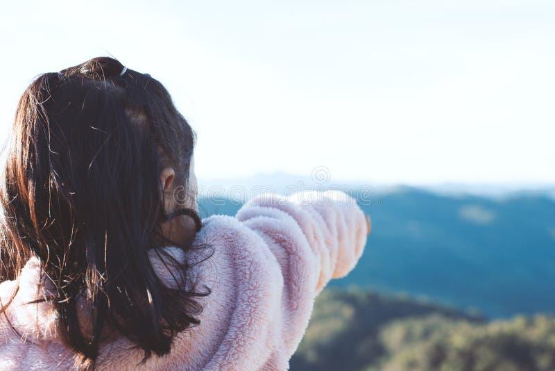 La vue arrière de la petite fille asiatique d'enfant a mis dessus le manteau soulèvent son bras image libre de droits
