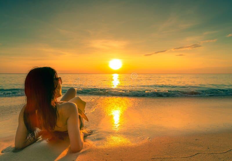 La vue arrière de sexy, apprécient et détendent le bikini d'usage de femme se trouvant sur la plage de sable avec le chapeau de p photographie stock libre de droits