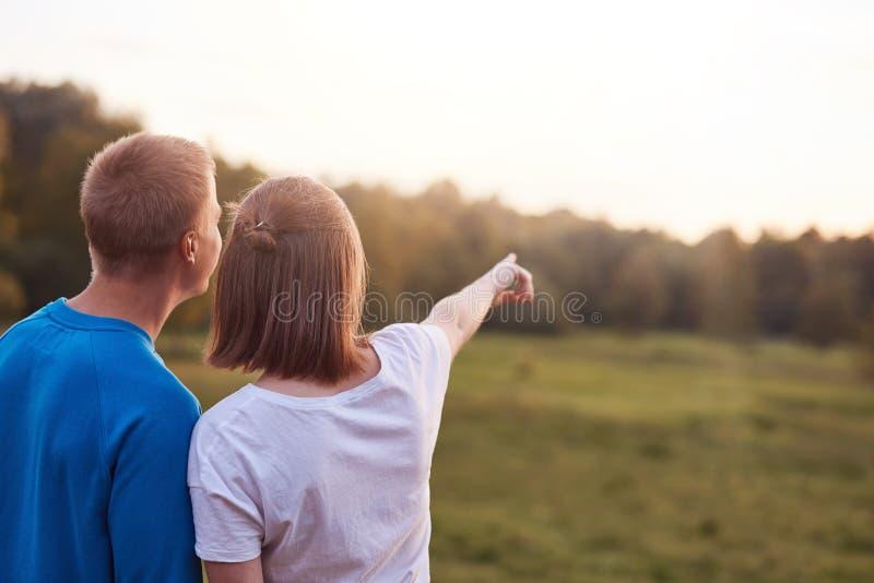 La vue arrière du type affectueux et de son support d'amie étroitement entre eux, regard à la distance, admirent la nature tandis images libres de droits