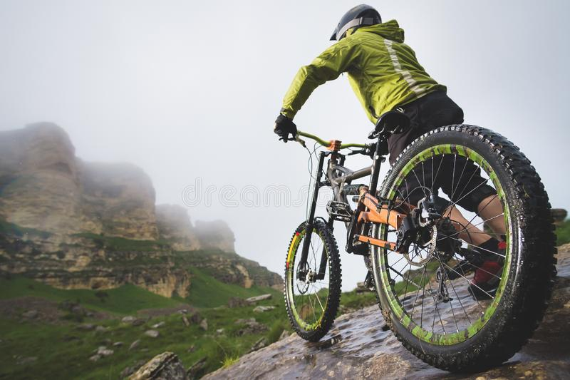 La vue arrière grande-angulaire d'un homme sur un vélo de montagne se tient sur un terrain rocheux et regarde une roche Le concep photos libres de droits