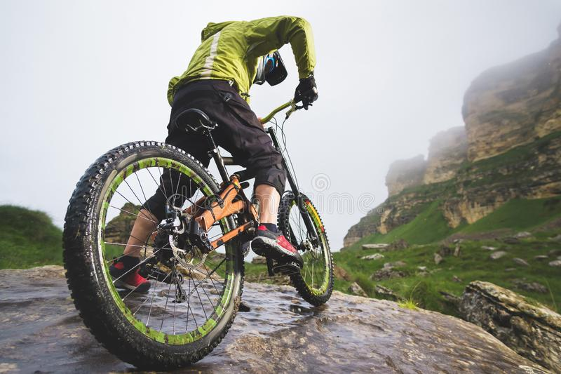 La vue arrière grande-angulaire d'un homme sur un vélo de montagne se tient sur un terrain rocheux et regarde une roche Le concep image libre de droits