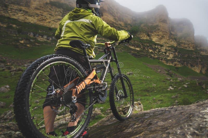 La vue arrière grande-angulaire d'un homme sur un vélo de montagne se tient sur un terrain rocheux et regarde une roche Le concep photo libre de droits