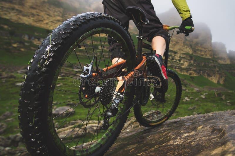 La vue arrière grande-angulaire en partie un homme sur un vélo de montagne voyage sur le terrain rocheux Le concept d'un vélo de  photographie stock libre de droits