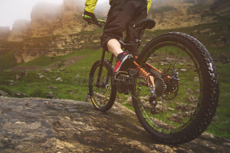 La vue arrière grande-angulaire en partie un homme sur un vélo de montagne voyage sur le terrain rocheux Le concept d'un vélo de  photos stock