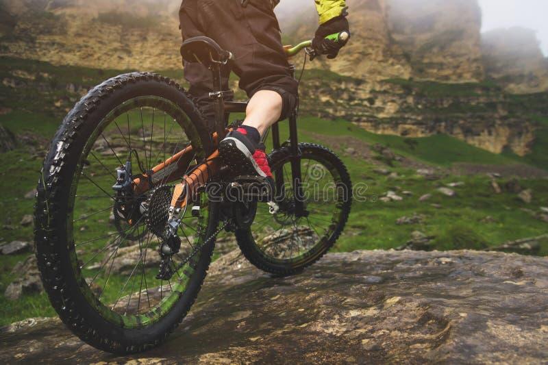 La vue arrière grande-angulaire en partie un homme sur un vélo de montagne voyage sur le terrain rocheux Le concept d'un vélo de  image stock