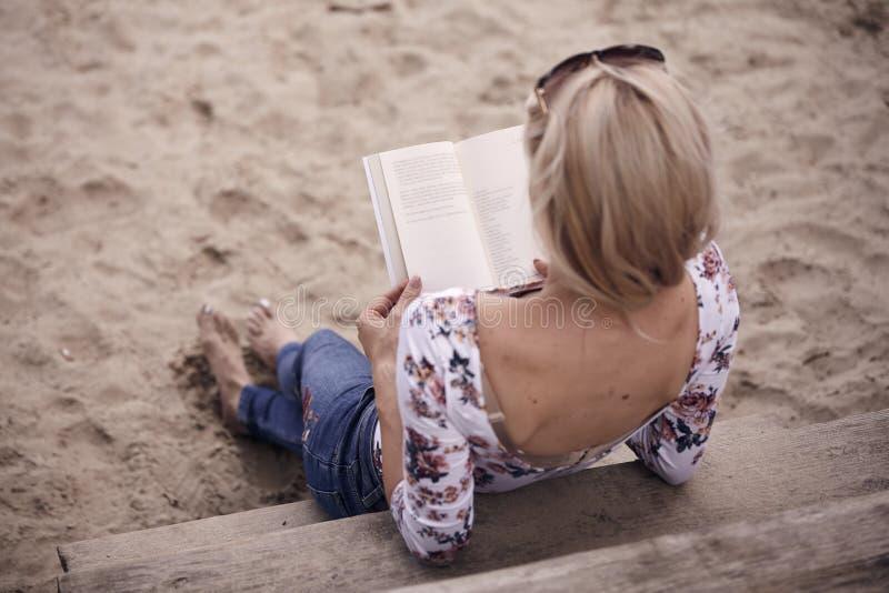 La vue arrière, un dos de jeune fille, étendant la détente sur le sable fait un pas, lisant un livre image libre de droits