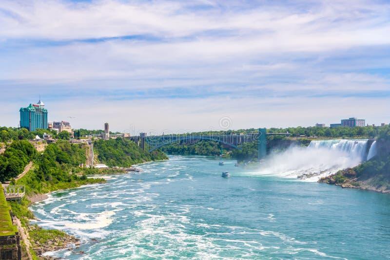 La vue au pont international d'arc-en-ciel au-dessus de la rivière Niagara avec l'Américain tombe et le voile nuptiale tombe au t photographie stock libre de droits