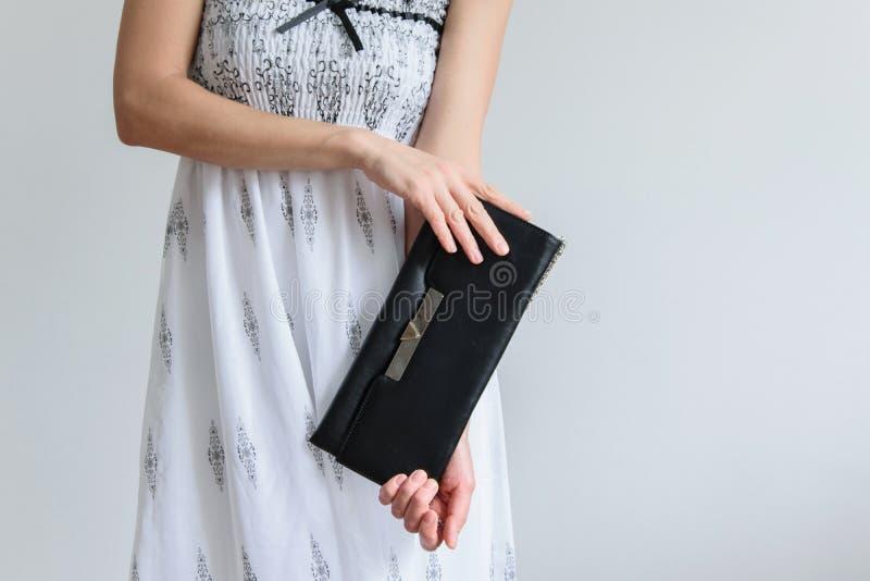 La vue avant de culture de la jeune femme à la mode s'est habillée avec la longue robe et tient un sac à main photo libre de droits
