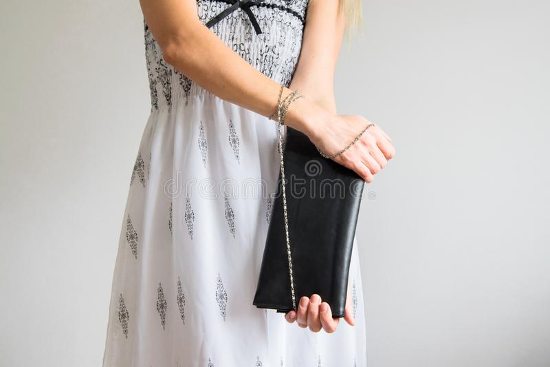 La vue avant de culture de la jeune femme à la mode s'est habillée avec la longue robe et tient un sac à main photographie stock