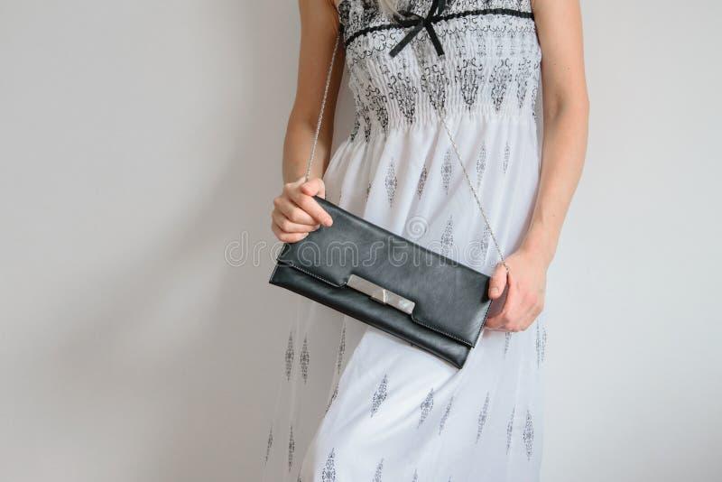 La vue avant de culture de la jeune femme à la mode s'est habillée avec la longue robe et tient un sac à main images stock