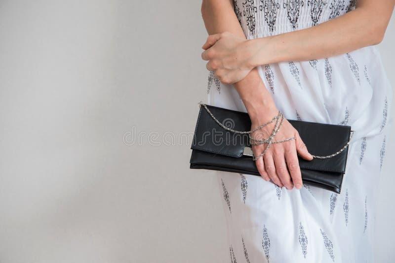 La vue avant de culture de la jeune femme à la mode s'est habillée avec la longue robe et tient un sac à main photos stock