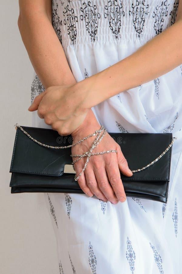 La vue avant de culture de la jeune femme à la mode s'est habillée avec la longue robe et tient un sac à main images libres de droits