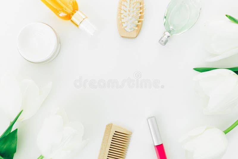 La vue avec des cosmétiques, le parfum, les peignes et les tulipes fleurit sur le fond blanc Composition en blogger de beauté Con photos libres de droits