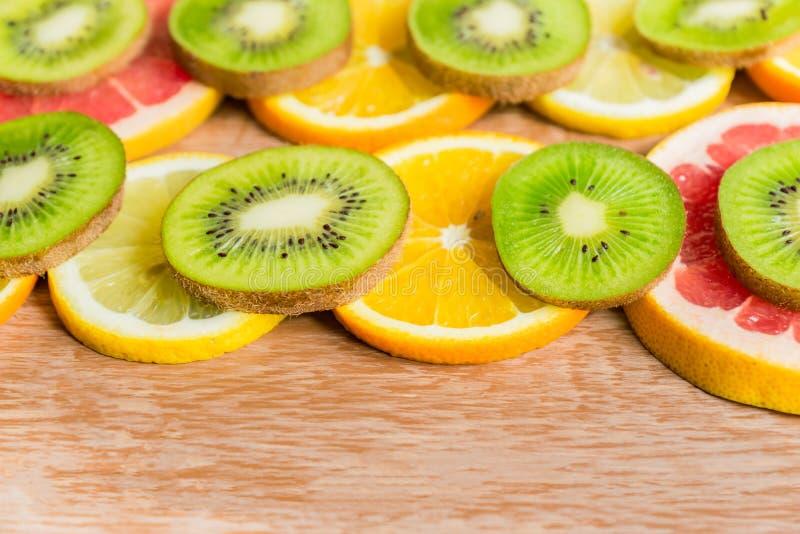 La vue avec la tranche d'oranges, citrons, kiwi, pamplemousse wppden dessus le fond photographie stock libre de droits