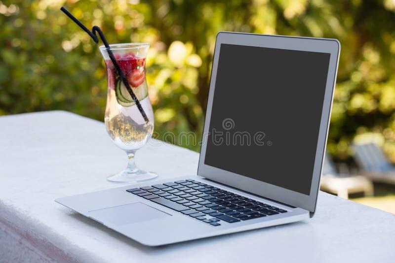 La vue courbe de l'ordinateur portable et le cocktail boivent au restaurant photographie stock libre de droits