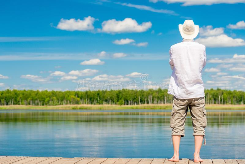La vue d'un jeune homme piny de pin avec les pieds nus se tient sur un en bois images stock