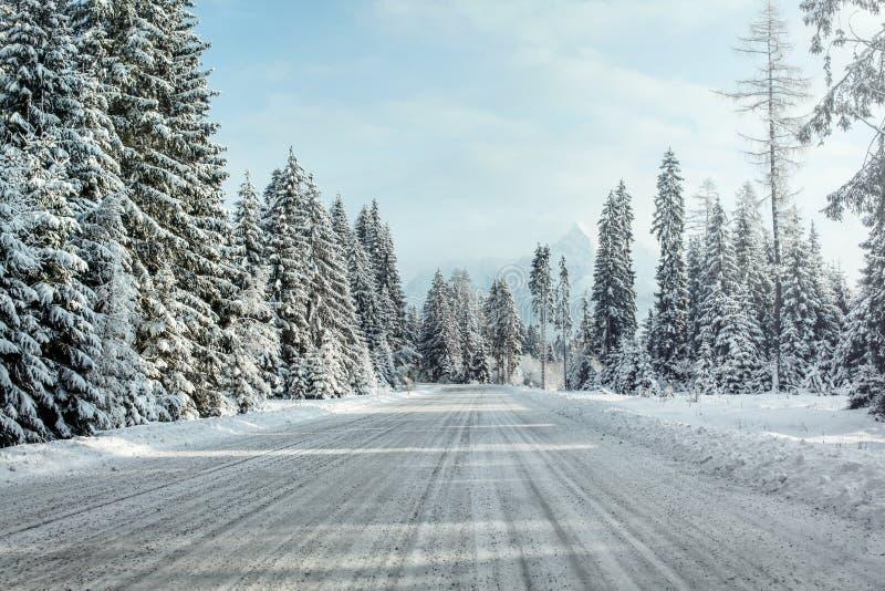 La vue d'une équitation de voiture par la neige a couvert la route d'hiver image stock