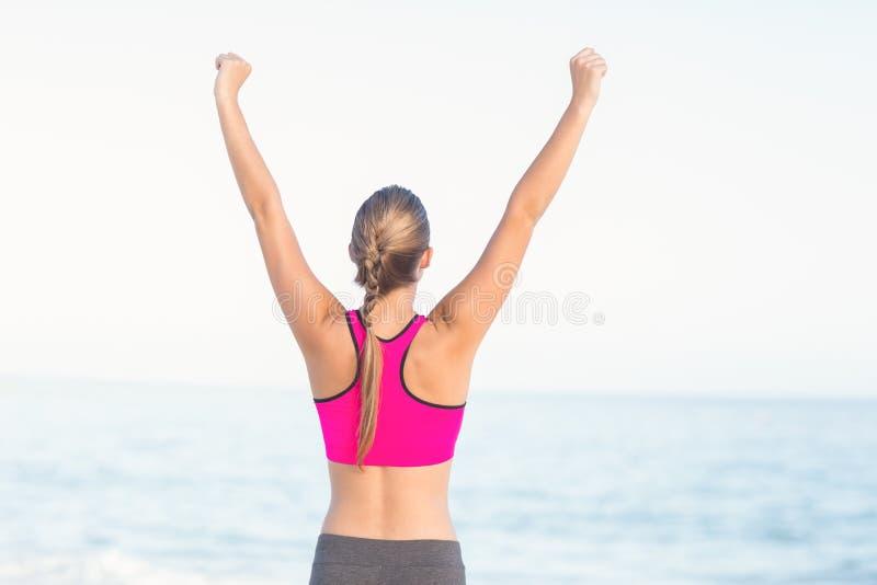 La vue d'usage de la femme d'ajustement regardant la mer avec des bras montent photo libre de droits