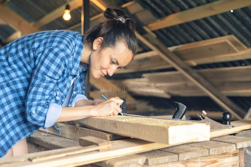La vue de côté d'un charpentier de femme dessine sur une ligne de coupe de conseil en bois images libres de droits