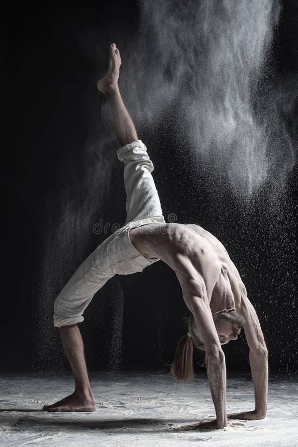 La vue de côté du jeune homme de caucaisanl établissant, faisant le yoga ou les pilates s'exercent Pose de pont, Urdhva Dhanurasa photographie stock libre de droits