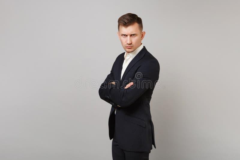 La vue de côté du jeune homme sérieux d'affaires dans le costume noir classique et de la chemise tenant des mains s'est pliée d'i images libres de droits