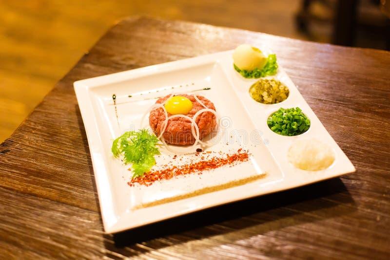 La vue de côté du plat a compris la viande crue, le jaune d'oeuf, la laitue, les épices, les verts et les oignons images libres de droits