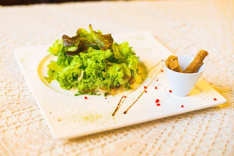 La vue de côté en gros plan de la salade et du pain sec décorés de la sauce et placés sur la table blanche image stock